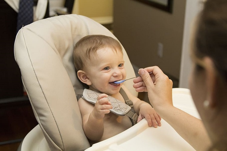Baby eating first food happily seating on high chair