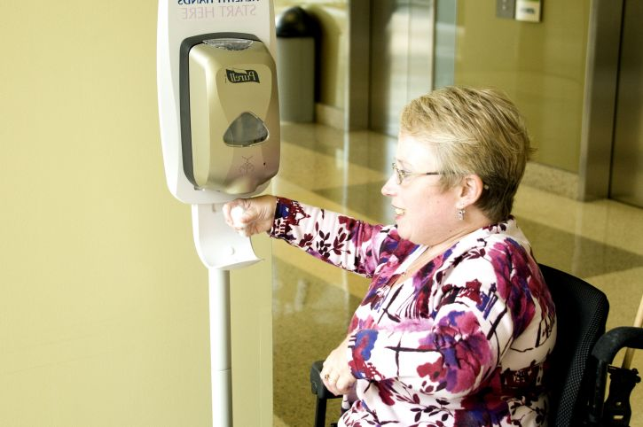 Lady using hand sanitizer from an automatic sanitizer dispenser