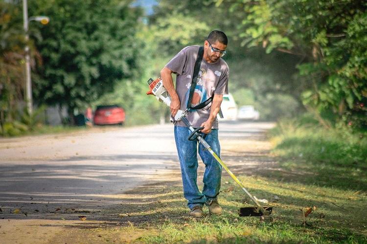 Person Cutting Grass Using Brush Cutter Machine