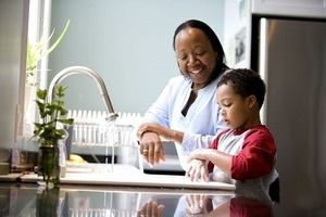 boy enjoys the washing of hands with his mother using hand sanitizer